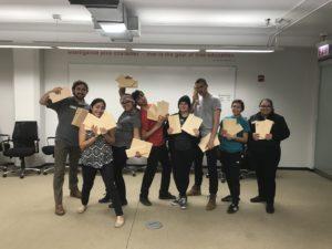 Participants in a company self-defense program show off the boards they broke